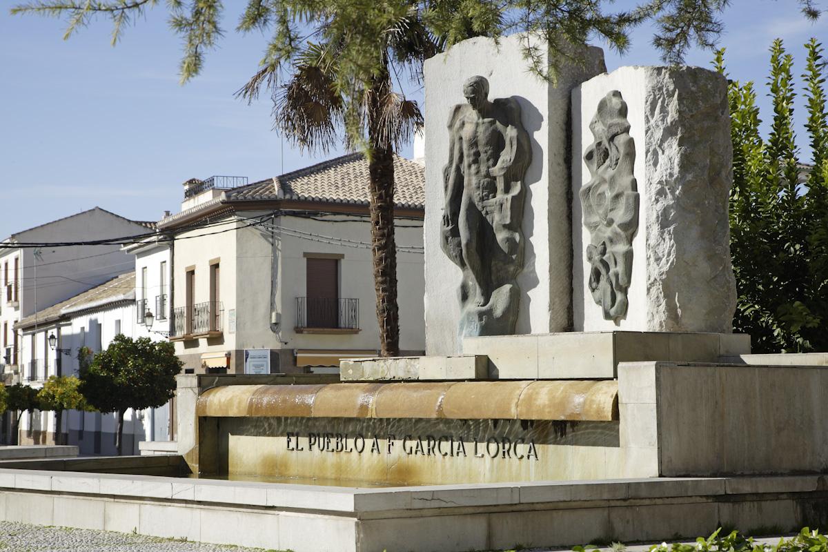 Sculpture of Federico García Lorca located on the Paseo del Prado promenade of Fuente Vaqueros. In the background, the poet's birthplace.