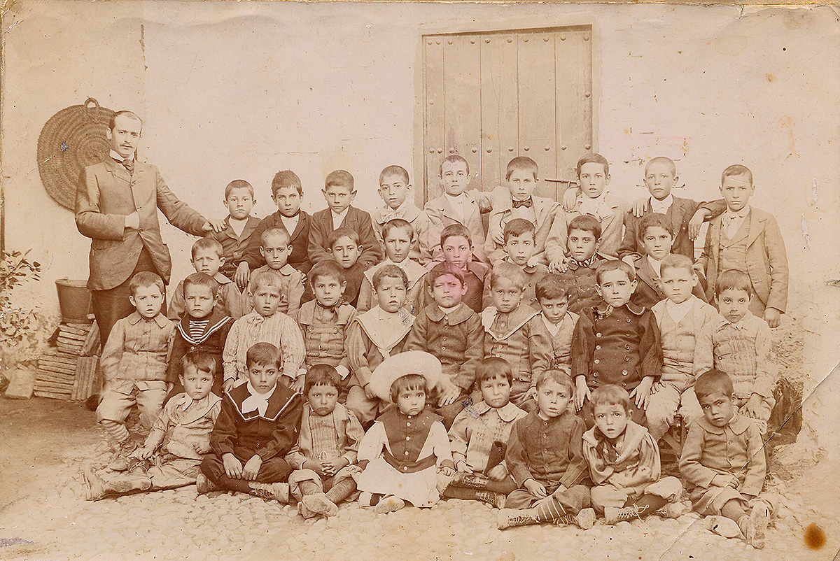 Photo of the students of the kindergarten of Fuente Vaqueros, with Federico García Lorca sitting on the floor and wearing a big hat. Their teacher Antonio Rodríguez Espinosa poses with them.