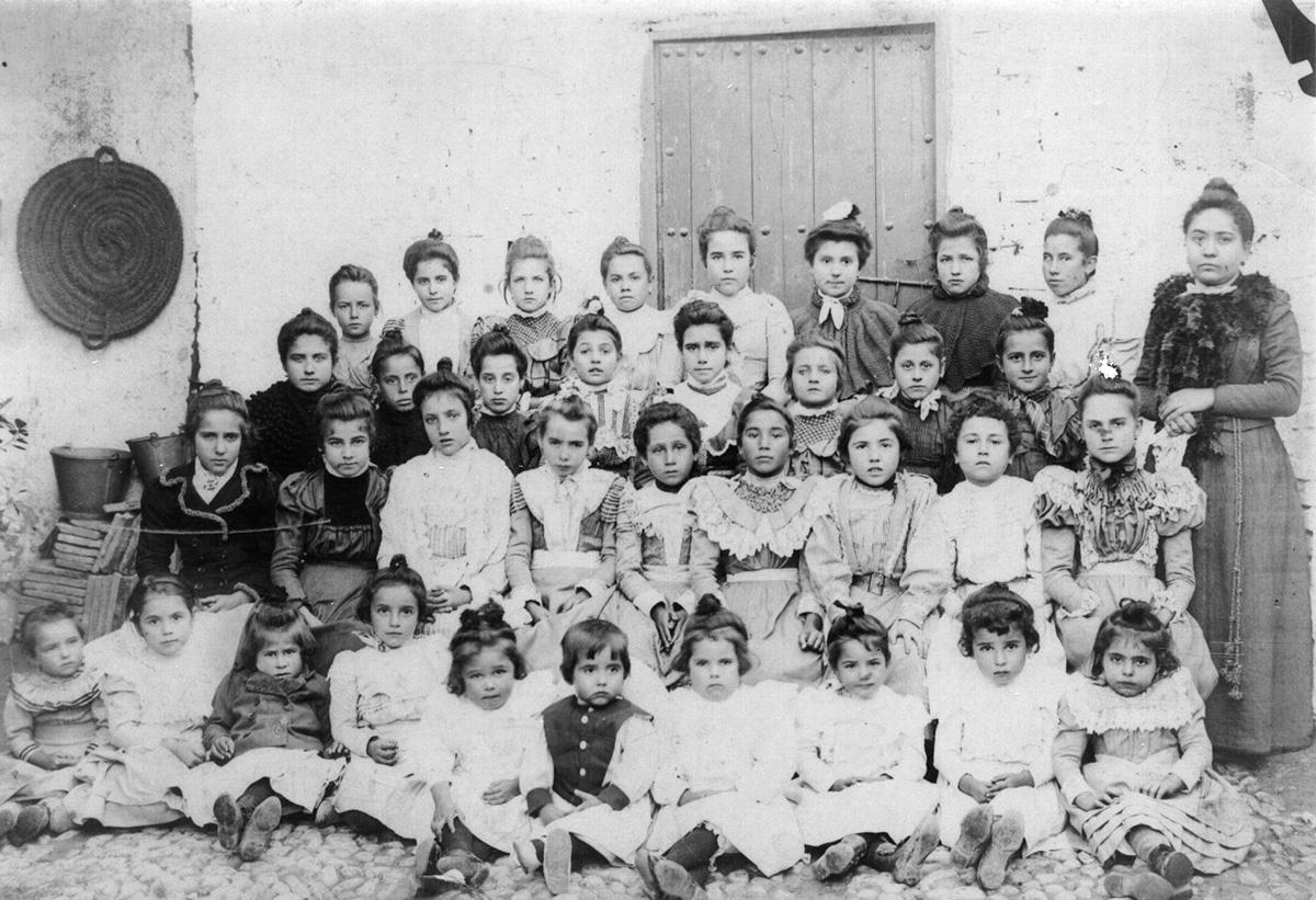 Federico, sentado en el suelo en el centro, posa con las niñas del parvulario de Fuente Vaqueros.